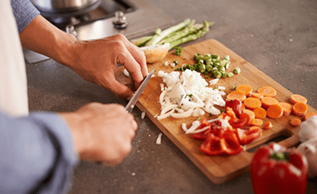 Man cutting vegetables on a wooden cutting board